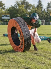 A Storm defender rips down the tackle wheel during defensive drills during practice Tuesday, Aug. 22, at Sauk Rapids-Rice High School.