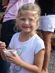 Isla Ray, 6, enjoys frozen yogurt donated by Orange Leaf Yogurt. Isles of Capri residents who had been dealing with the aftermath of Hurricane Irma got together Tuesday evening for a hot meal and cold beer and frozen yogurt, courtesy of local merchants.