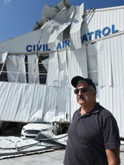 Civil Air Patrol commander Major Robert Corriveau in front of the destroyed facility. The CAP's hangar at the Marco Island Executive Airport was smashed by an extremely local event during Hurricane Irma.
