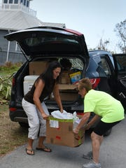 Voluneers Jerra Minning, left, and Betsy Johnston unload donations at 1994 Sheffield Ave. The Marco Patriots came together as local residents banded together to offer hurricane relief.