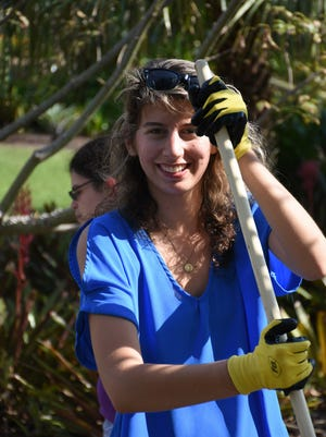 Tori pauses her raking long enough for a smile. A group from the Trailblazer Academy at the Foundation for the Developmentally Disabled made a field trip to the Naples Botanical Garden Wednesday, volunteering to help clean up storm damage before the garden reopens on Sunday.