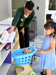 Eloue Latouche from Publix helps Ashley Cintora, 4, find items from a shopping list at Family Literacy Day on Saturday, Nov. 4.