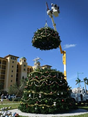 An LCEC crane hoists a section of the tree into place. Workers from Condee Cooling and LCEC helped Christmas Island Style volunteers erect the new tree in Veterans Community Park.