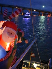 Santa and his chopper wave aboard Grand Pelican. Despite the cancellation of the Christmas Island Style Christmas boat parade, a group of decorated vessels toured the Marco River on Saturday night.