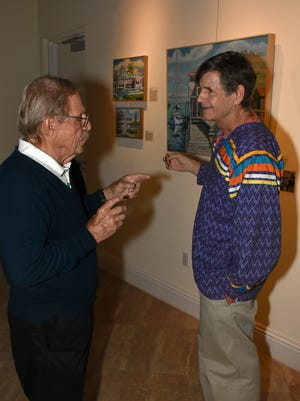 """Artist Paul Arsenault, right, talks with Kris Helland. The Marco Island Historical Museum opened an exhibit Wednesday evening called """"Coastal Trade,"""" featuring paintings and artifacts from Arsenault's collection."""