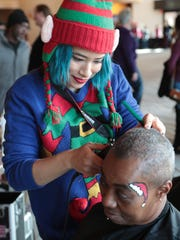 Nesheba More gets a trim from Ashley Ramirez at the Well in the Desert Christmas event, December 25, 2017.