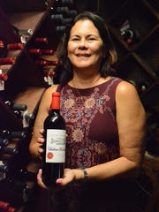 File: Lisa Meurgue shows a bottle from a vineyard her