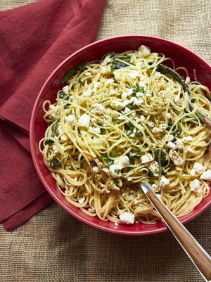 A dish of linguine with lemon, feta cheese and basil.