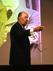"""Elliott Katz in front of a photo of Nazi production minister Albert Speer. Katz presented a lecture at Hodges University entitled """"Thank You for the Bomb, Mr. Hitler"""" on Jan. 11, part of a series sponsored by the Holocaust Museum of Southwest Florida."""