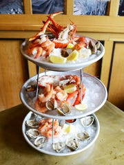The triple seafood tower from the Lobster Trap features shrimp, lobster, king crab legs, clams and gulf oysters.