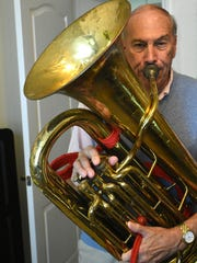 Longtime Marco Island Strummers bandleader Wes English blows a blast on the tuba at his beachfront condominium. English spent a lifetime juggling music and medicine.