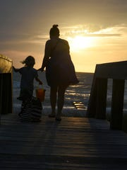 Lindsey Pruitt of Fort Myers hits the Naples beach at sunset with son Landon, 3. The Florida legislature has approved a measure that, with congressional approval, would move the Sunshine State to Daylight Saving Time year Õround.