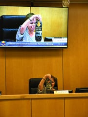 "Chair Ruth McCann displays a ""Do Not Disturb"" sign to shield sea turtles from lights. The Marco Island Beach and Coastal Resources Advisory Committee met Wednesday morning in the city council chambers."