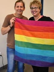 Naples Pride founder and president Cori Craciun, left, and  Debbie Gaffoli with one of the original rainbow flags created by artist Gilbert Baker. Volunteers met Tuesday evening to coodinate the upcoming 2nd annual Naples Pride Festival, which will be held Saturday, June 2 at Cambier Park in Naples.