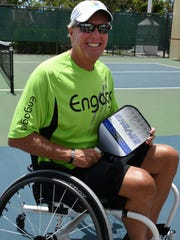 Wheelchair pickle ball player Mike O'Leary, who plays against standing opponents, on the court. Pickle ball facilities at the city's racquet park have been upgraded to allow wheelchair access.