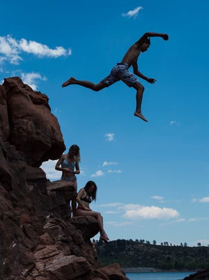 A boy jumps off the rocky cliffside into the water while hanging out with friends at Horsetooth Reservoir on July 18, 2018. While the heat might tempt a lot of us to go cliff-jumping this summer, Larimer County Department of Natural Resources reminds people that the activity is dangerous and illegal at Horsetooth.