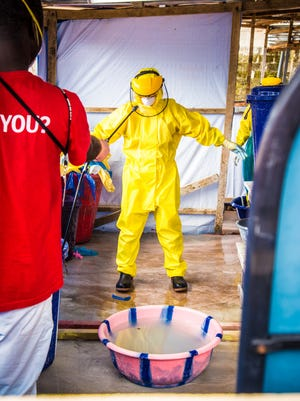 A healthcare worker in protective gear is sprayed with disinfectant after working in an Ebola treatment center in the west of Freetown, Sierra Leone, Thursday, Oct. 16, 2014.