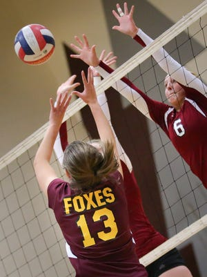 Alex Meidl (13) of Omro and Annika Gereau (6) of Winneconne battle at the net. The Winneconne Wolves hosted the Omro Foxes in a Division 2 Volleyball Tournament Tuesday, October 21, 2014.