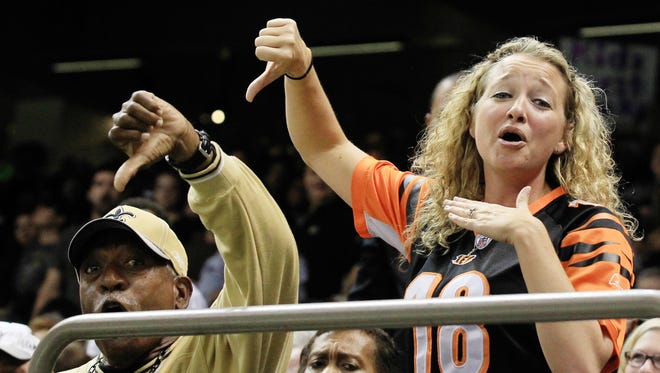 Cincinnati Bengals fan Christa Barrett gives a thumbs down to Saints fan Tony Williams, who returned her thumbs down gesture, after he snatched a Bengals touchdown ball away from her during an NFL game Sunday, November 16, 2014, at the Mercedes-Benz Superdome in  New Orleans, La.