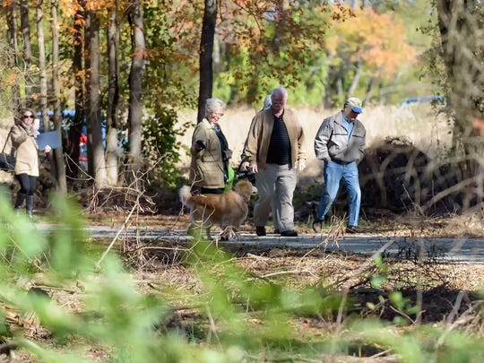 Visitors walk down the scenic trail towards the wildlife viewing platform at Thousand Acre Marsh, near Port Penn, on Friday.
