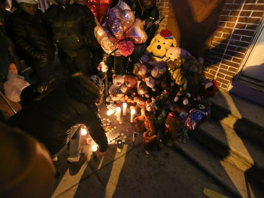 Mourners light candles Wednesday in front of the North