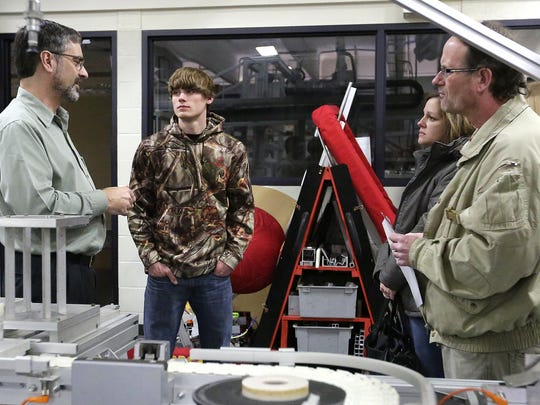 Jeff Quackenboss, left, an instructor at Moraine Park Technical College, speaks with Christopher and Becky Justmann of Juneau and Paul Vanderscheuren, center, of Fond du Lac during a jobs open house March 3. Moraine Park, a two-year college, is partnering with several four-year University of Wisconsin schools to help more students get the training they need for jobs.
