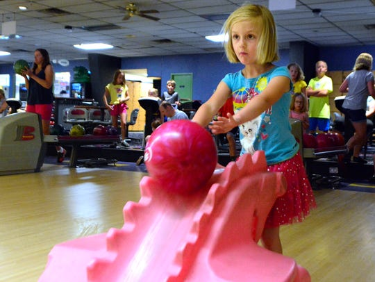 Briar Peterson, 4, of Dover, rolls the ball while bowling