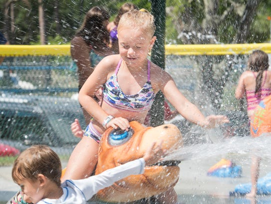 Ryleigh Watts, 7, is drenched with water as she sits
