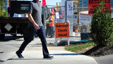 A pedestrian walks across Division Street around a closed sidewalk in Nashville in 2015.