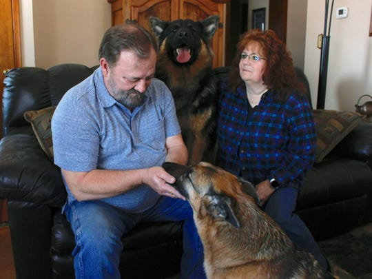 Joe and Deb Colgan sit with their German shepherds
