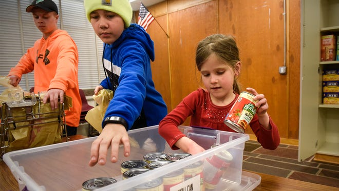 Lydia Neisinger stocks a supply of canned food as volunteers pack meals as part of the Rocori Action Packs program Tuesday, March 21, in Cold Spring. The program supplies meals for elementary students over the weekends.