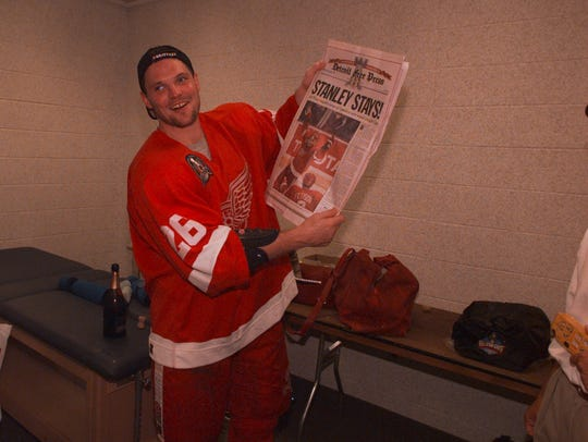 Red Wings' Joe Kocur holds the Free Press special edition in the locker room after their Game 4 sweep of the Washington Capitals on June 16.