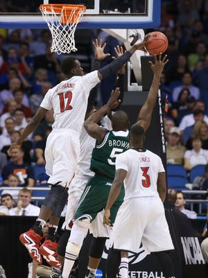 U of L's Mangok Mathiang, #12, gets a hand on a shot by Manhattan's Rhamel Brown, #5, during their NCAA game at the Amway Center in Orlando, Fl. Mar. 20, 2014