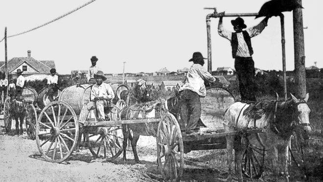 Water vendors known as barrileros wait in line to fill their casks with the city's new drinking water at a standpipe on the bluff, believed to be about 1895. The barrileros used 55-gallon barrels on two-wheel carts, usually pulled by mules or donkeys. This standpipe was at Sam Rankin and Mestina.