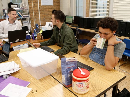 Demarius Fisher (right) sips his coffee Wednesday, May 17, 2017, as he does his government classwork along a classmate and teacher inside the Flex Academy classroom at Roosevelt High School in Des Moines. Fisher graduated this spring.