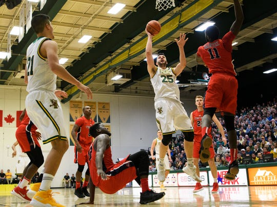 Vermont's Drew Urquhart (25) takes a shot over Stony Brook's Junior Saintel (11) during the men's basketball game between the Stony Brook Seawolves and the Vermont Catamounts at Patrick Gym on Saturday afternoon January 13, 2018 in Burlington.