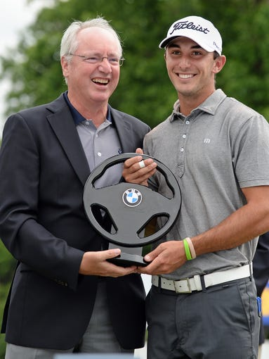 President of BMW Manufacturing Manfred Erlacher presents Max Homa with the BMW Charity Pro-Am Championship trophy after Homa won the tournament by 1 stroke Sunday, May 18, 2014  at the Thornblade Club in Greer.