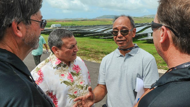 Gov. Eddie Calvo, facing left, and Consolidated Commission on Utilities Commissioner Simon Sanchez chat with NRG Renew's Senior Vice President Hazen Burford and Guam Project Manager Bill Alexander during a ribbon cutting ceremony for NRG's Dandan Solar Project in Inarajan on Wednesday, Oct. 7.