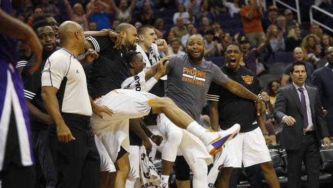 Phoenix Suns players react to a dunk by forward Jon Leuer over Sacramento Kings center DeMarcus Cousins during preseason NBA action at Talking Stick Resort Arena in Phoenix October 6, 2015.