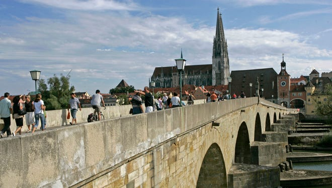 The spires of the Regensburg cathedral are seen while pedestrians cross the Gothic bridge over the Danube river in Regensburg, southern Germany.