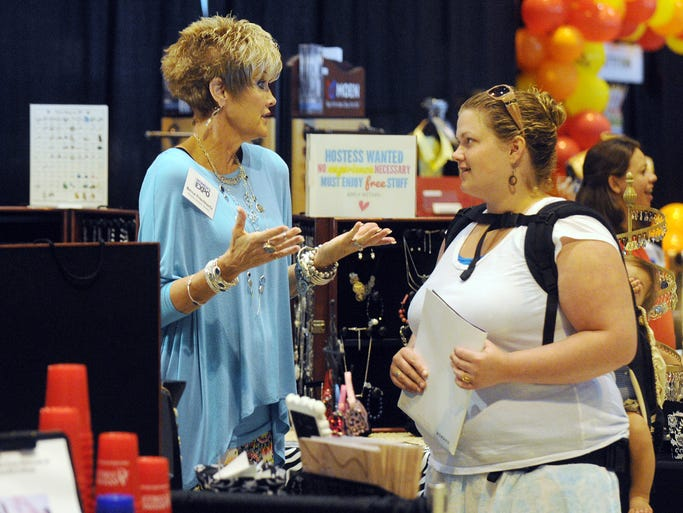 Silpada Designs Jewelry's Becca Frischhertz, left, speaks  to Katie Santos about the store's products Saturday during the second annual Pine Belt Women's Expo at the Lake Terrace Convention Center.