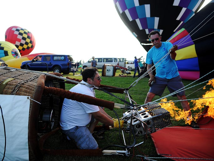 Jon Shelton, left, of West Des Moines, Iowa, works to take off with his balloon with the help of his dad, Bob Shelton, of Indianola, Iowa, at the start of Saturday evening's balloon race during the 39th annual Great Plains Balloon Race on Saturday, Aug. 16, 2014, in Sioux Falls, S.D. Jon went on to win Saturday evening's race by dropping his baggie from his balloon and landing it closest to the target. Saturday evening's race started at Kenny Anderson Park and competitors dropped their baggies on a target near the Humane Society on East Benson Road.