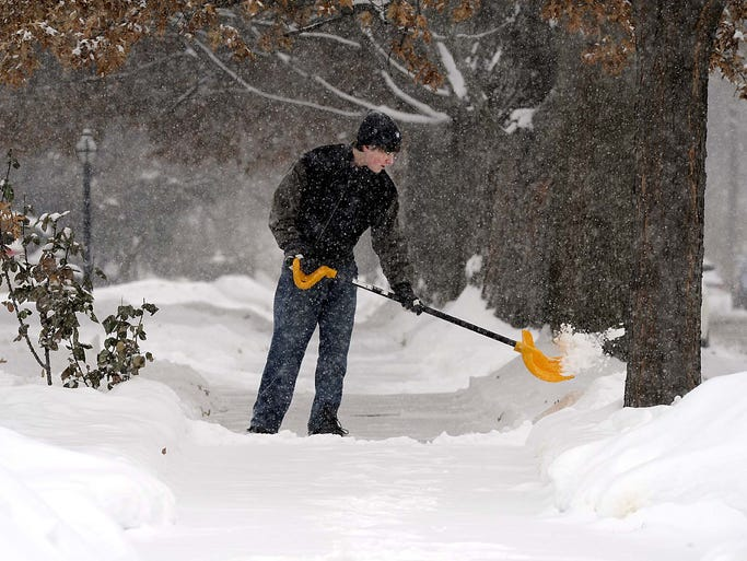 Zach Schmidt, on a day off from school, cleans a sidewalk on Walnut Streetin Kingston, Pa.,assnow falls Dec. 17, 2013.