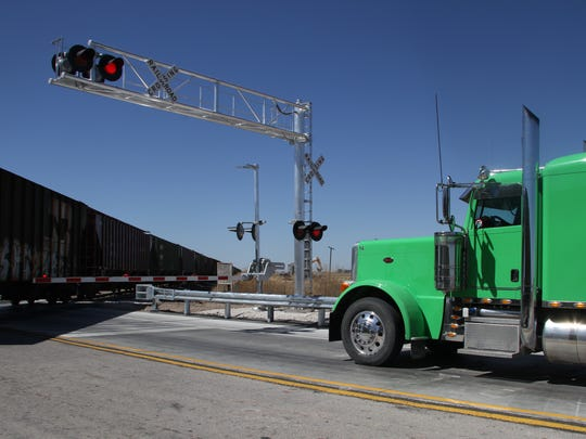 A semi-truck waits at the railroad crossing at U.S.