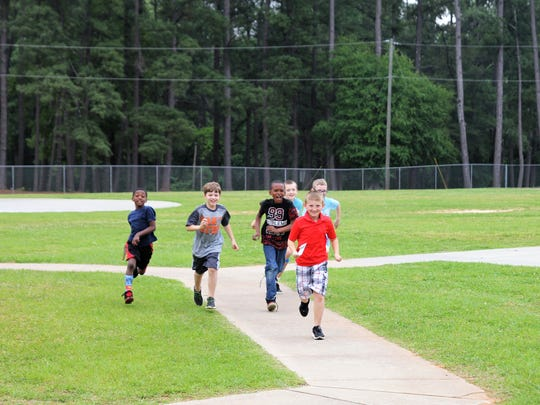 Cole Fowler leads a group of his friends as they run back to class after he memorialized his mother.