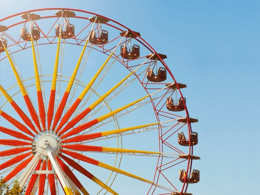 Large red and yellow Ferris wheel at a fair under a blue sky