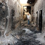 An employee of Doctors Without Borders (Medicins Sans Frontieres) stands in the ruins of the Kunduz, Afghanistan hospital bombed in error by U.S. forces, Oct. 16, 2015