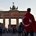 A man with a Turkish flag wrapped around his shoulder in front of Brandenburg Gate in Berlin, Germany.