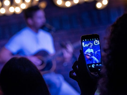 A fan takes a photograph with her cellphone as Jake Owen performs during an event at WKDF on July 18, 2016, in Nashville.