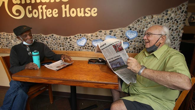 Randy Carr, left, and Ron Olah share a coffee and a newspaper Saturday morning, Oct. 31, 2020, at Hannah's Coffee House on East Marion Street in Shelby.